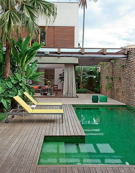 flores tropicais jardim:Além da piscina, o muro também foi incorporado ao ambiente, como uma